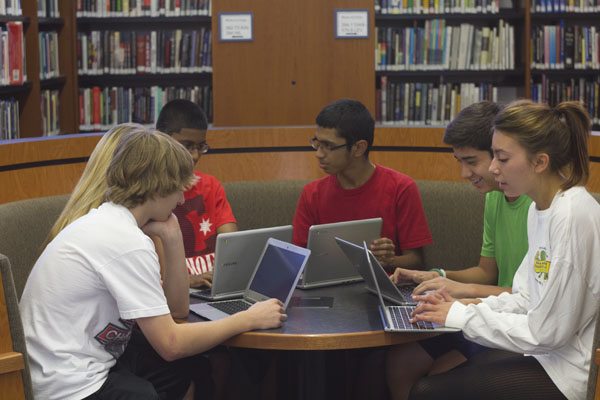 In the IMC, students collaborate using their Chromebooks. No longer limited to the computer labs, freshmen, sophomores and juniors can access the internet and Google Apps anywhere in the school through their devices. Photo by Cormac O'Brien.