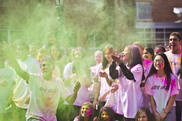 COURTYARD COLOR: Armed with packets of neon powder, Desi Club leader Tom Olickal sends more color into the crowd. Members of Desi Club and Eastern Religions students commemorated Holi, the Hindu spring festival of color, April 2.