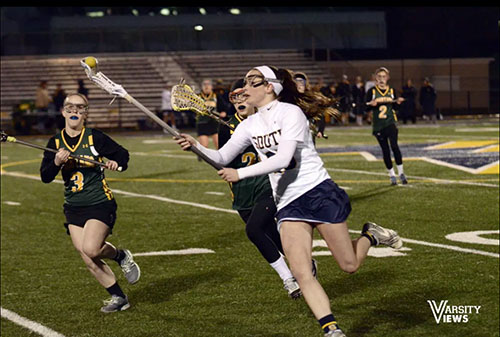 FAST AND FURIOUS: Focusing on gaining possession of the ball, junior midfielder Sarah McDonough looks to outrun the GBN defenders. The Titans defeated the Trevians 14-8 on March 17. Photo courtesy of Varsity Views; www.varsityviews.com
