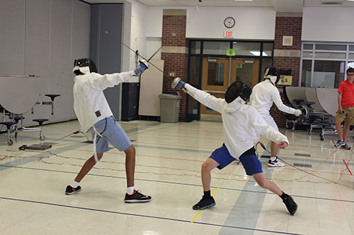 FIERCE FENCING: Fencing club members practice by competing in pairs. Club practices always use full body gear for protection.