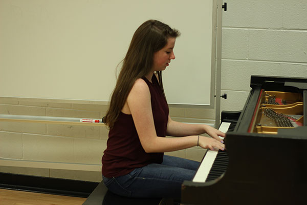 Concentrating on the keyboard, Claire Demorest plays the piano in South's choir room. Demorest is involved in many of South's choirs and musical productions.
