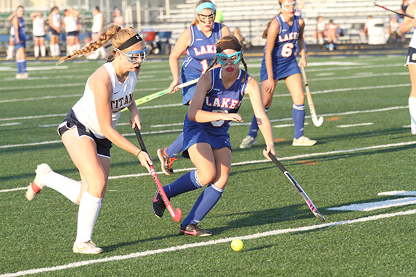 GOGGLE GAL: Running around a Lake Forest defender, junior defender Megan Dillon looks to pass to a teammate. At the end of the game the score was tied 2-2 and the Titans lost in overtime to the reigning state champions 3-2.