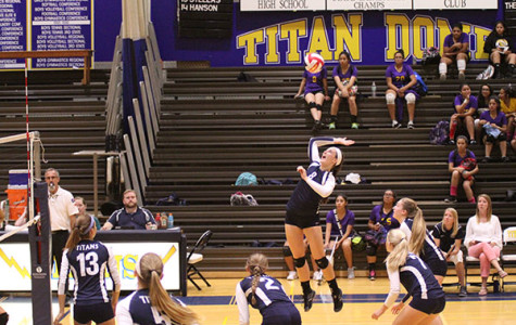 BUMP, SET, SPIKE: Jumping into mid-air, junior Zimmie Frerichs sets up to spike a ball against Waukegan on Sept. 16. The Titans won with a final score of 25-6 and 25-12.