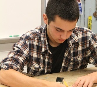 Using various tools, a male student designs his next project in jewelry class.