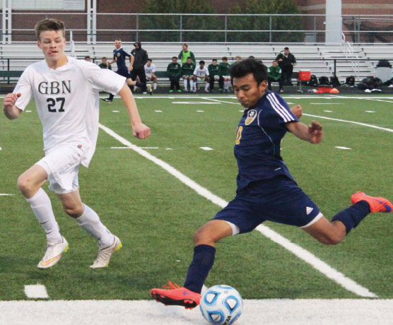 MOHAWK MEN: Striding towards the ball, senior captain Javier Ayala (left) looks to make a pass to a teammate down the field. Looking for an open player, senior captain Iñaki Bascaran winds up for a throw-in (right). The Titans shaved and styled their hair into mohawks in preperation for the playoffs, but eventually lost to GBN in double overtime in a penalty kick shootout. Photos by Jacqueline DeWitt