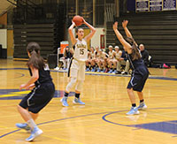 Looking past a defender, junior Carie Weinman (middle), prepares to make an overhead pass to an open teammate on the inside. Weinman is a returning starter. The Titans beat Prospect High School by a score of 50-39 on Dec. 12.