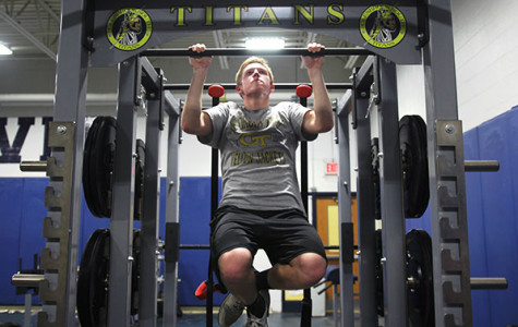 BUILDING STRENGTH: In gearing up for their spring season, junior Jake Smiley utilizes a new pull-up bar to improve his strength for baseball.