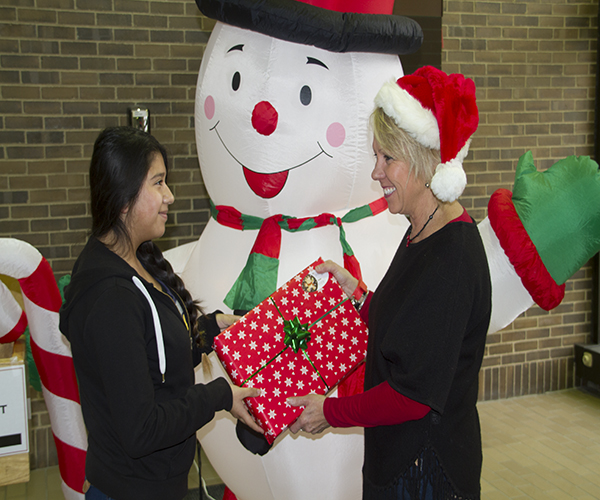 GIFT OF GIVING: Freshman Jennifer Vargas receives a gift from Glenview Youth Services, an organization that has provided financial assistance to her and her family during the holiday season for many years. Photo by Ashley Clark