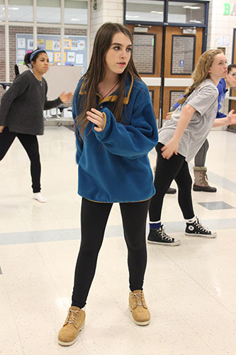 Putting her hips and arms into a body roll, Alana Swarigen practices with the other members of De La Cru for their routine.