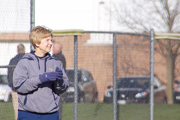 Standing on the third base line, Kay Sopocy, varsity softball coach, smiles while clapping her hands during a game against Evanston on April 12. Sopocy is finishing off her 24th year of coaching for the GBS softball team.