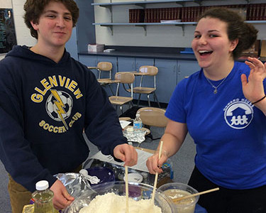Posing while baking Challah, a traditional Jewish bread oftentimes served on holidays, junior Rebecca Spector, Israeli Club president, helps to mix the dough with sophomore Jake Hershenhouse. Israeli Club meets to discuss the prevalence of Israeli culture through activities and meetings. Photo courtesy of Rebecca Spector