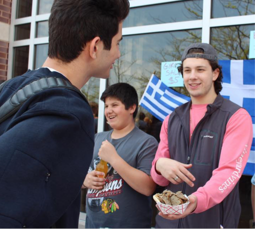 GRINNING GREEKS: Offering a traditional Greek dish to other students, senior George Maroutsos serves gyros to Spring Fling attendees. Other GBS clubs such as Girl's Letter Club and Ciao Club made an appearance at the event.