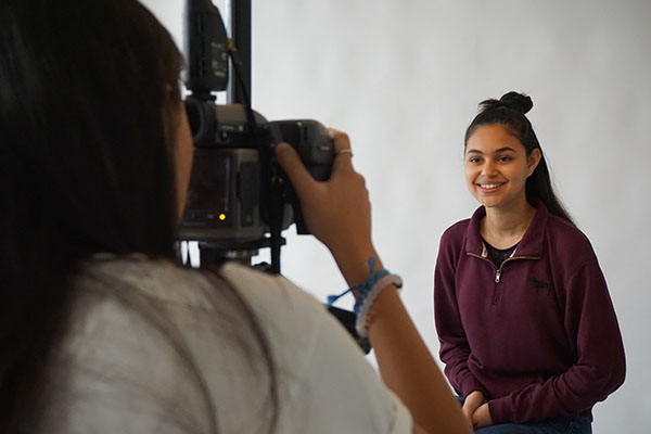 SMILING SUQI: Posing in one of the newly constructed photography rooms, sophomore Jena Suqi grins for sophomore Yoon Kim. Expanded space for the elective is one of a number of changes made as a result of the merge.