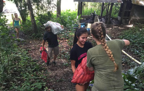 Twenty-Four Carrots:   Working with a fellow trip participant, sophomore Emma Noffke hands off a bag of carrots to feed the animals she cares for on her trip.  This summer she traveled to Guatemala through the organization The Road Less Traveled.  Photo courtesy of Emma Noffke