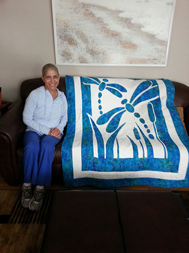 """GRINS AND GIFTS: Appreciating her new present, science teacher Linda Kocian poses with a quilt given to her by fellow colleague Suzanne Webb as a """"get well"""" gift. Kocian received lots of support from South's staff when she was diagnosed with Multiple Myeloma. Photo courtesy of Jennifer Friedmann"""