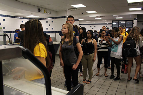 hungry   high   schoolers:   Queued up in the cafeteria, students wait to be served at food court stations. Quest has recently changed their policies regarding negative balances.