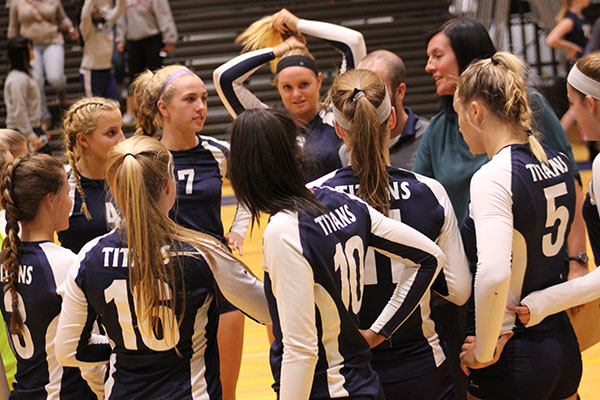 Huddle  in  for  the  win:  Listening to new head coach Kelly Dorn, the women's volleyball team huddles and discuses their play after their win against the Niles North. The Titans played and defeated the Vikings on Sept. 27 ending by scores of 25-5 and 25-14.