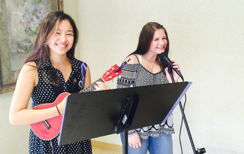 Smiling through   serendipity:  Strumming and singing, juniors Audrey Hwang and Zoë Gunderson respectively rehearse for their upcoming shows. The two met in 2016 through the Glenview Rock House and soon established themselves as a band entitled Serendipity.