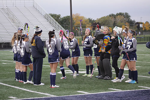 SISTER SUPPORT: Preparing for a game, the women's field hockey team draws on each other for support. Women's field hockey is just one sport that utilizes the big and little sister program at South.