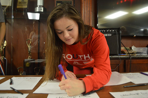 CAN-DO ATTITUDE: Preparing bidding sheets for the Canned Food Drive Silent Auction on Nov. 18, Carolyn Kuhn, senior class treasurer, assigns a value to an item. The Silent Auction was one of the various events organized by Student Council in order to reach the goal of 100,016 cans.