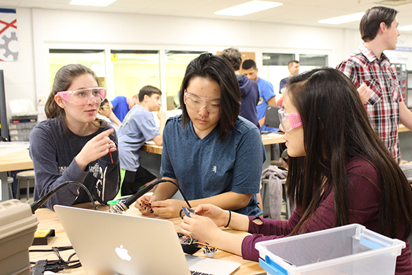GIRL GENIUSES: Discussing and planning, sophomore Sophie Nathanson, senior Elizabeth Park and junior Katheryn Woo develop a prosthetic hand. The prosthetic hand that Society of Women Engineers designed and created was donated to e-NABLE, an organization that sends prosthetics to those in need.