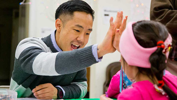 KEY CLUBIN' KOO: High-fiving a student from Passages Charter school, Josh Koo, incoming assistant principal of student services, praises a young participant at an Eat 'N' Read event. According to his coworkers and students, Koo's energy and compassion make him qualified to assume his new position starting with the 2017-2018 school year.
