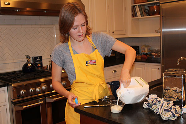 Cautiously measuring the amount of milk needed for her recipe, junior Kate Voss  works to create a delicious meal. Voss is the president of South's new club Cooking for a Cause, which combines cooking with community service. Photo courtesy by Kate Voss