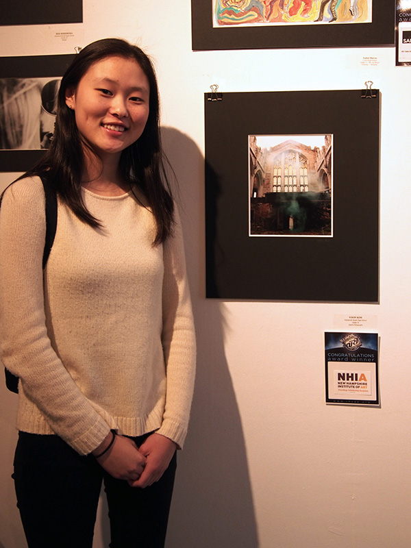 "SMILING FOR   SCHOLARSHIPS: Posing in front of her Illinois High School Art Exhibition (IHSAE) photo, sophomore Yoon Kim shows her submission entitled ""Beauty in Decay."" At the competition, Kim received a $1000 scholarship to attend a summer workshop at the precollege of the New Hampshire Institute of Art."