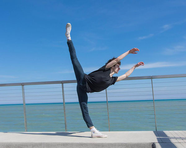 LOUNES BY THE LAKE:  Bending forward with one leg in the air and his arms spread out, junior Lounes Landri executes a Penché. Landri started dancing when he was in seventh grade, and this summer, he will be attending a summer program at The Juilliard School.