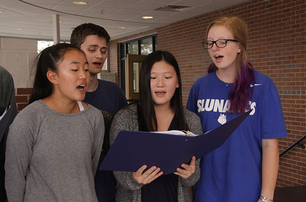 SERENADING SCAT THAT: Reading their music intently, (from left to right) sophomore Jenna Kim, seniors Micheal McNeela and Yenny Ha and junior Ellie Eavenson sing in South's only jazz group, Scat That. This group is directed by co-choir director Andrew Toniolo, pictured above.