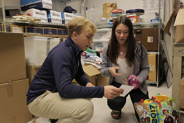 Sorting cans, senior Abby Grant, student body president, and junior representative Matthew Baumstark work to box donations from students and staff. This year, instead of accepting both money and cans, Student Council is moving toward only food donations.