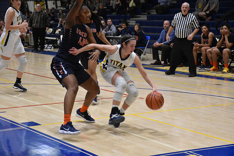 HEAD IN THE GAME:  Driving past an Evanston defender, senior Lizzy Shaw dribbles on the Titans home court. The Titans fell to the Evanston Wildkits 54--31.