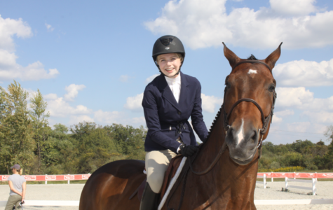 Smiling for a photo with her horse, sophomore Caroline Sultz prepares for a show. According to Sultz, riding is very a competitive sport and deserves more recognition. Photo courtesy of Caroline Sultz.