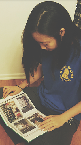 Junior Isabel Baik looks at family photos of her relatives in Korea. Baik believes the distance between her family allows her to appreciate each moment they are physically together.