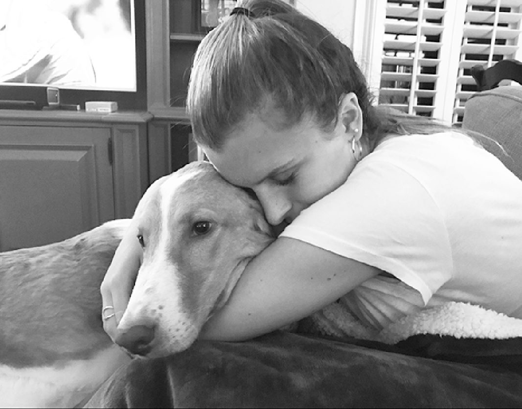 CAROLINE TO THE RESCUE: Laying on her couch, Sophomore Caroline O'Shaughnessy embraces her rescue dog, Dakota, whom her and her family adopted three years ago. O'Shaughnessy encourages families to consider adopting rescue animals instead of buying from designer breeders. Photo courtesy of Caroline O'Shaughnessy