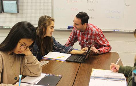 OUTGOING O'MALLEY: Sitting with his students, Mathematics Teacher John O'Malley helps freshman Sabrina Penepacker with her work. O'Malley received the Illinois Promising New Teacher of Mathematics Award for his creative and interactive method of teaching.