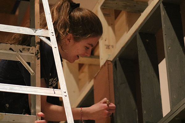CREATIVE CONSTRUCTORS:   Balancing on top of a ladder, sophomore Hannah Dobos carefully paints the background set. All students are welcome to participate in set construction along with South's Stage Crew.