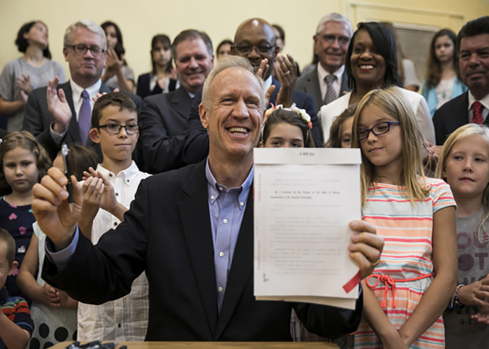 RAMBUNCTIOUS+RAUNER%3A+Holding+a+newly+signed+law%2C+Governor+Bruce+Rauner+smiles.+Rauner+passed+a+new+budget+for+Illinois+that+included+cutting+P.E.+requirements+in+public+schools.