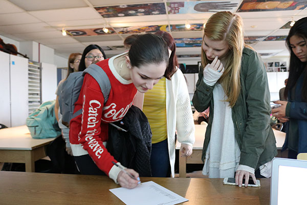 PRODUCTIVE POWWOW:  Leaning over a table, senior Angela Golota and junior Oliva Wilas sign into a National Art Honors Society meeting. Stephanie Fuja, fine arts teacher, brought a chapter of the National Art Honors Society to South this year to bring attention to art students' work.