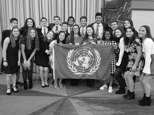 DISTINCT DELEGATES:  The GBS Model United Nations Team poses at the National High School Model United Nations Conference (NHSMUN) in New York City (left). After the team was honored with an Award of Distinction, Katie Roberts, co-president of Model UN, and senior Tricia Katsamakis smile at the camera (right). The Award of Distinction is the highest honor a team can earn at NHSMUN and was only awarded to three schools across the country. Photos courtesy of Leah Dunne