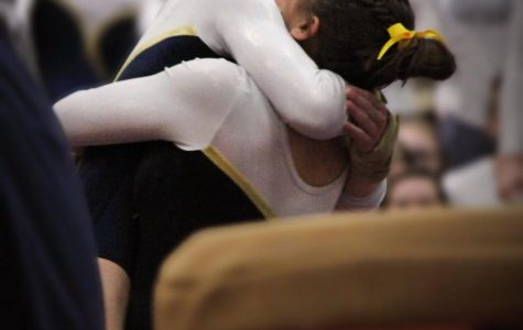 ECSTATIC EMBRACE:  Celebrating their win, sophomore Jenna Hartley and senior Bebe Haramaras hug after finishing a routine. The girls went on to place 3rd at state.