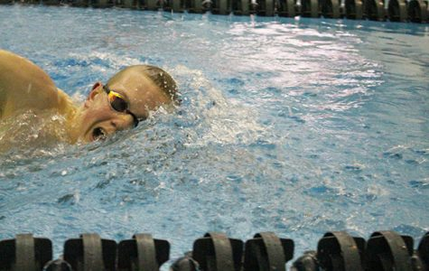 Completing his stroke, junior Zach Spalding competed at the Titan Senior Night.