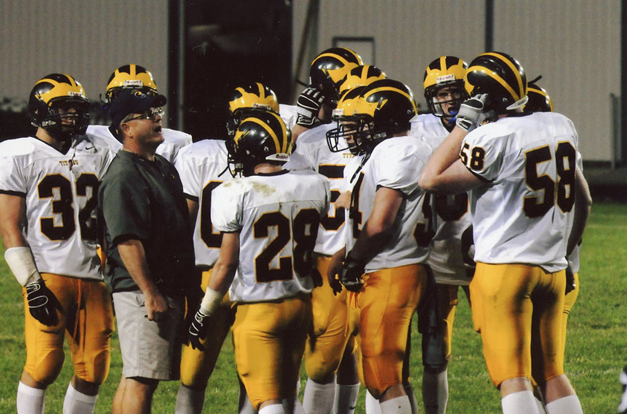 TIME'S UP FOR TITAN: Talking to a football player, Mike Noll, former head coach of Glenbrook South's Football Team and social studies teacher, spends time on the football field with the team. Noll has spent 14 years working at South.