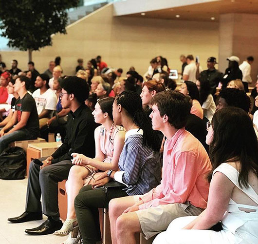 What   a   view:  Sitting amongst his fellow summer interns, senior Brendan Garvey (in the salmon shirt) attends a viewing party at an Apple store in downtown Chicago. Through this internship at Apple, Garvey hopes to explore his options for a possible future career.