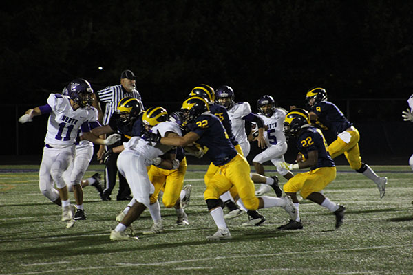 Blocking the Niles North defense, the Titans protect sophomore Zack Herndon (22) as he attempts to score a touchdown. The team played Niles North for their homecoming game on Sept. 21 and won by a score of 41-0.