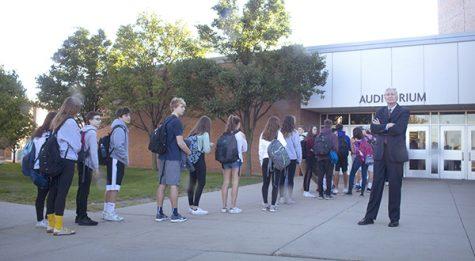 "it   can   happen   anywhere: Forming a line outside the auditorium doors, students wait for their belongings to be checked by faculty and administrators before school on Monday. Sept. 24 while Superintendent Dr. Michael Riggle supervises. This security measure was implemented after a message reading ""there will be a school shooting on September 25th 2018"" was found in a South classroom and reported on Sept. 20. Photo by Yoon Kim"