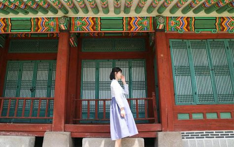 Happy Homes: Giggling in her country of origin, sophomore Seonghyun Kim poses in front of a building in South Korea.