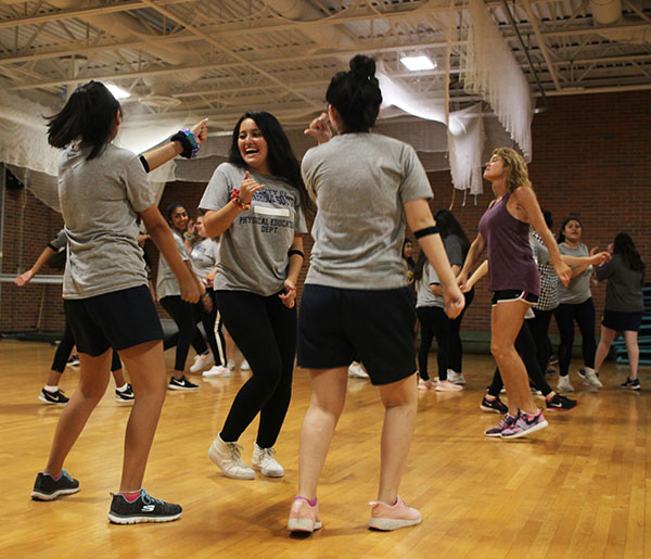 A For Effort: Dancing in PE class, junior Leila Khakpour (facing center) uses a heart rate monitor to track her activity level. At the end of last school year, heart rate monitors were introduced in some PE classes, and their use is continuing this year in freshman and sophomore classes.