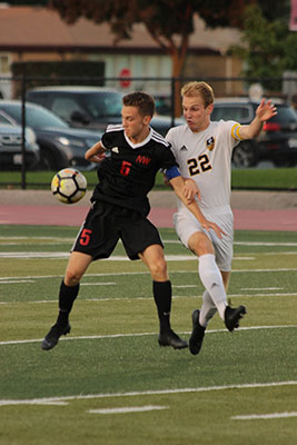 Defending a Niles West player, senior Gavin Morose fights for the ball.