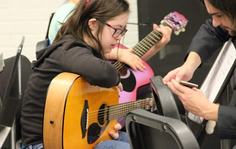 Guitar Guru: Resting her arm on the guitar, freshman Molly McNamara learns how to play with the help of Teacher's Assistant Jacob Lill. Guitar is a music elective that is offered at South that gives students the freedom to learn several songs of their choice.